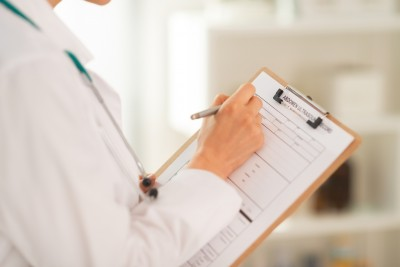 Closeup on medical doctor woman writing in clipboard