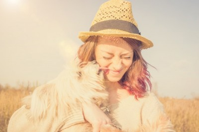 Puppy white dog is kissing its caucasian owner in the countryside - caucasian people - animal, people, lifestyle and nature concept